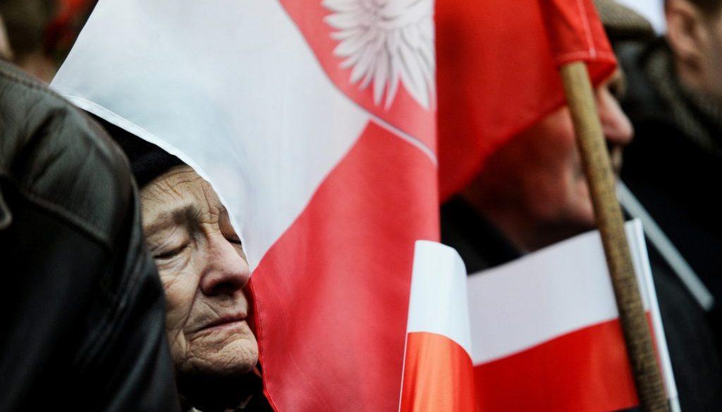 gillert maciej interfoto polka w podeszłym wieku z zamknietymi oczami oparta o flage polski